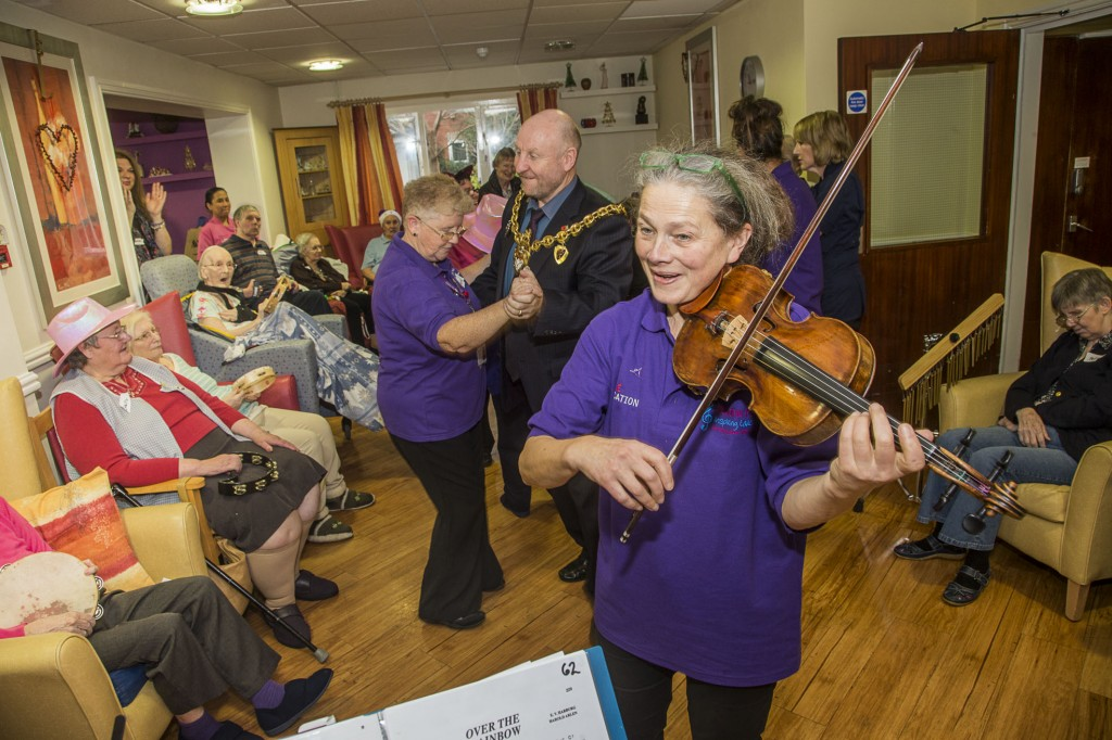 David Petri on keyboard and violinist Carfoline Abbott from the Halle with Pendine Park residents at Cae Bryn. The Mayor of Wrexham, Councillor Alan Edwards dances with carer Irene Monks.