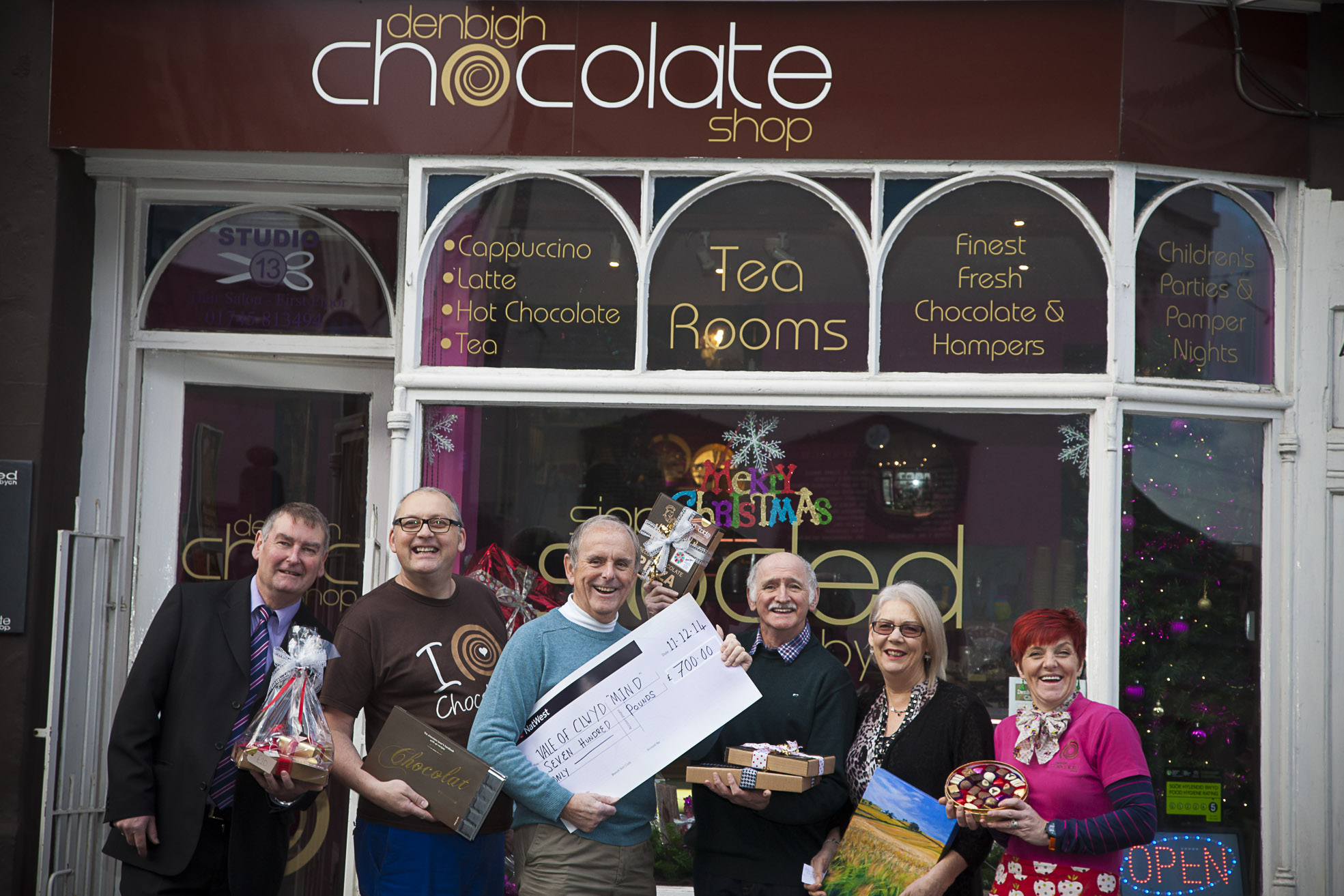 Pictured is Phil Williams, Acting Director, Mark Yound, Denbigh Chocolate shop, Barry William,Chair, Clwyd Wynn, Vice Chair, Carol Wynn Artist and Nia Lloyd-Jones from the Chocolate shop with £700 raised from a chocolate and wine tasting fundraiser.