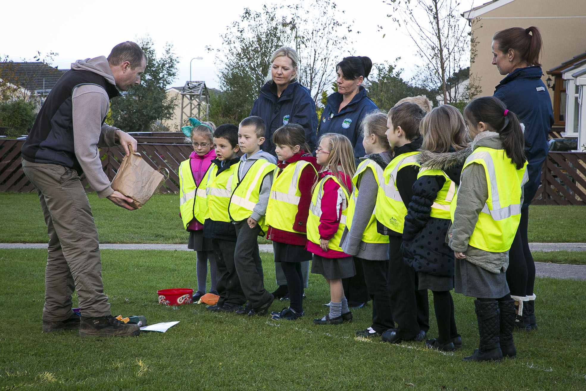 Cartrefi Conwy Peulwys Estate. Bulb planting. Children from the local primary school listen to instructions from with environemental development officer Matt Stowe.