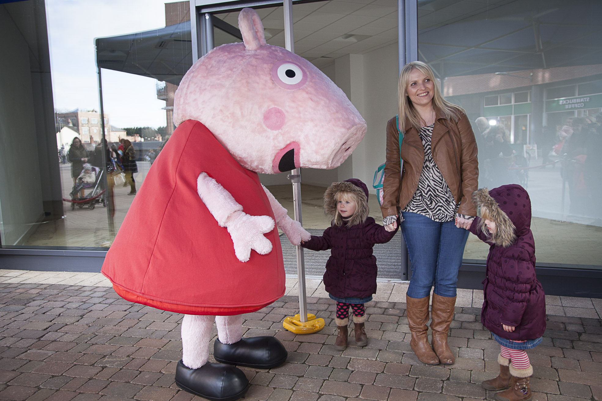 Peppa pig arrives at Eagles Meadow shopping centre, Pictured are Holly and Ffion Williams, three, with Mum Alison.