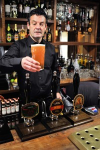 Mick Taylor, owner of Y Talbot pulling a pint behind the bar at Y Talbot.