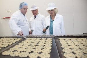 ROYAL VISIT TO VILLAGE BAKERY WREXHAM. Pictured is The Prince of Wales and the Duchess of Cornwall flipping Welsh cakes watched by Rob Glover,  production manager.