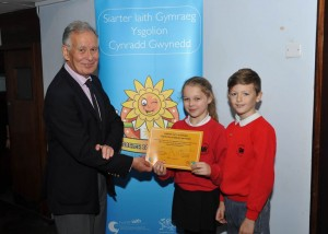 Councillor Peredur Jenkins, Gwynedd Council Cabinet Member presenting the Welsh Language Charter gold award certificate to Ysgol Cefn Coch, Penrhyndeudraeth pupils