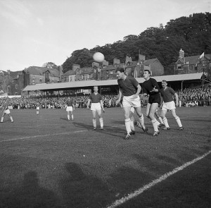 Iorys Griffiths defending with goal keeper, Len Davies behind him and captain Ken Birch watching from afar. Image from Geoff Charles' collection from the 1962 AC Napoli game in Farrar Road through the kindness of the National Library of Wales.