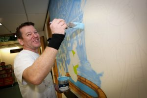 Artist Gary Drew creating pirate-themed giant artworks at the entrance to the Children's Department.