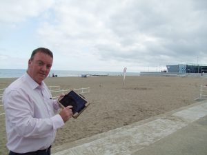 Cllr Mike Priestley, Cabinet Member for Communications checks the Wifi on Colwyn Bay waterfront.