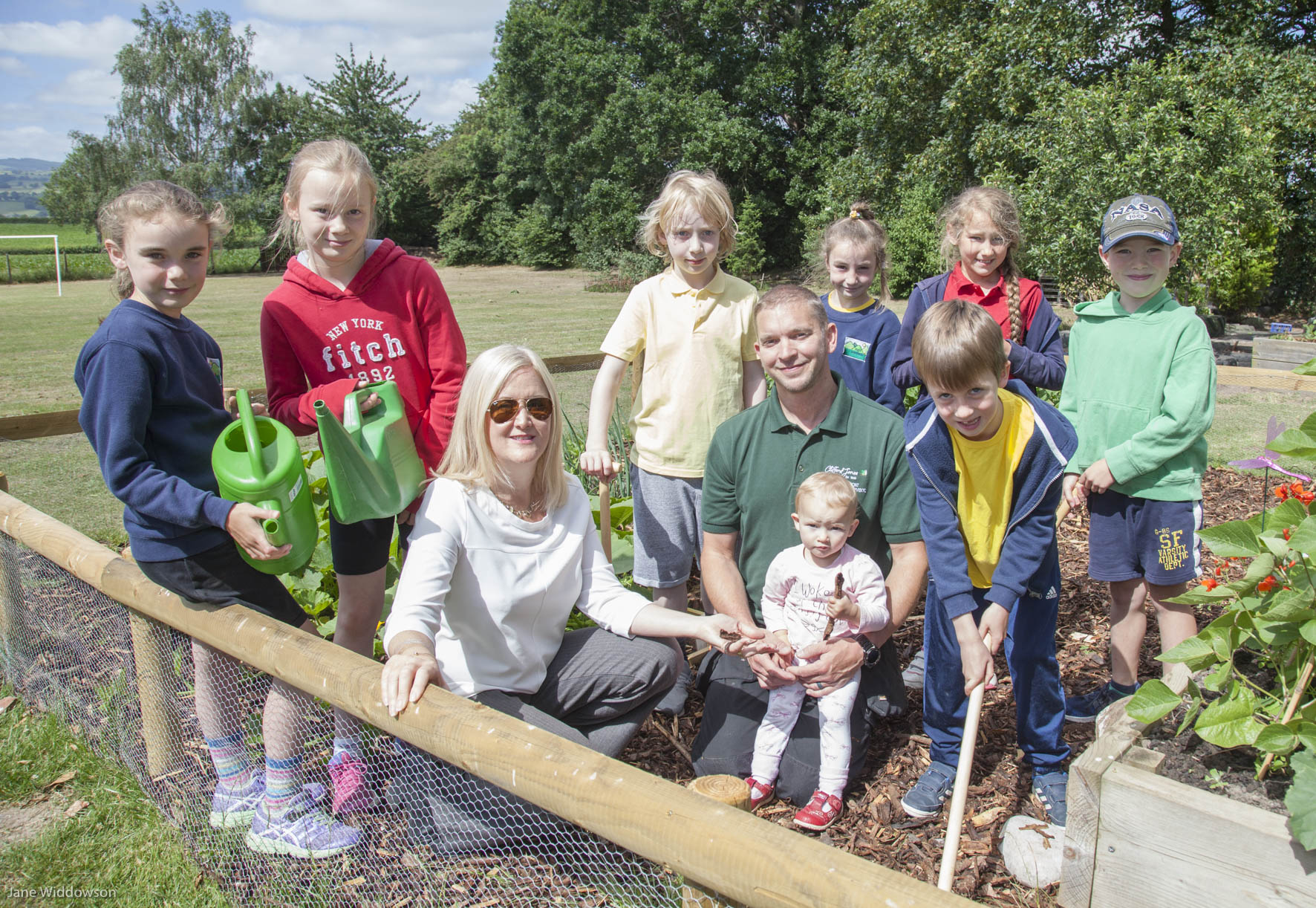 Members of the Llanbedr School Eco Group show off their garden to Clifford Jones Timber Director Sarah Jones Smith and Production Supervisor Michael Beaumont, a parent at the school, pictured with his daughter, Lilou, 18 months, Grace Meyman, 8, Beatrice Marston, 10, Harry Benjamin Williams, 8, Luciana Farinha, 9, Zoe Maddock, 8, Rhys Jones, 7, and Madoc Cotter, 7.
