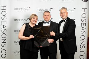 Rowland and Sian Rees-Evans from Penrhos Park receive their award from Hoseasons' head of product, Scott Drew