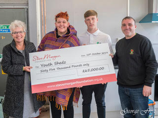 Jane Harris, left, presents the cheque to Youth Shedz.